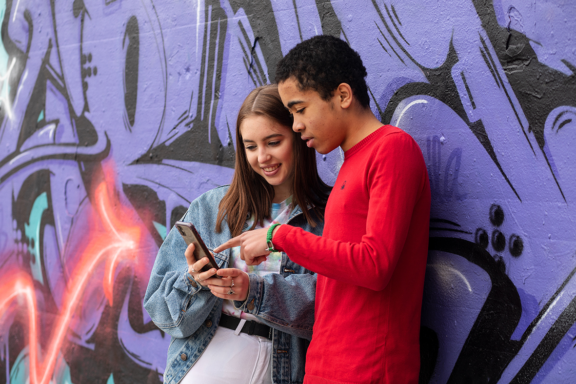 Deux adolescents regardant ensemble un smartphone.